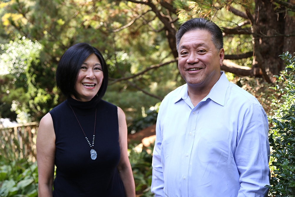lisa yang and hock tan stand smiling with foliage behind them